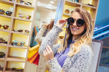 Happy woman buying sunglasses in shop.