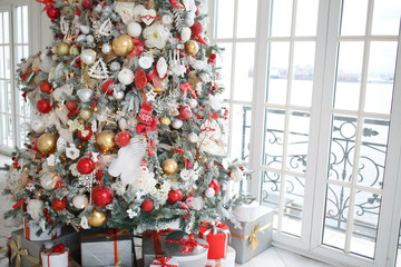 Christmas tree with a beautiful decor in a bright interior.