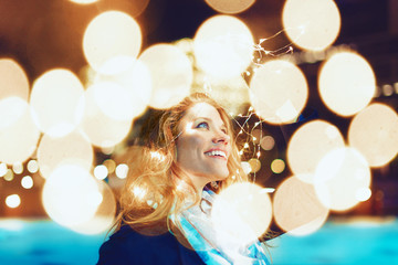 Happy young woman amazed by LED fairy lights at city outdoor