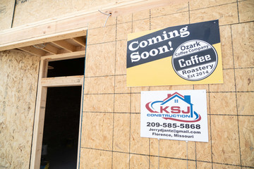 A sign proclaiming the new home of Ozark Coffee Company is seen on construction boarding in Sedalia