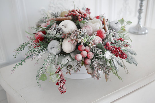 Winter decorative arrangement of fir branches and fruit in hoarfrost.