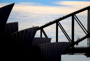 The roof of the Sydney Opera house can be seen in front of tourists as they climb the Sydney Harbour Bridge
