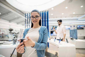 Woman holding in hands smart watch while standing in tech store and looking in camera.