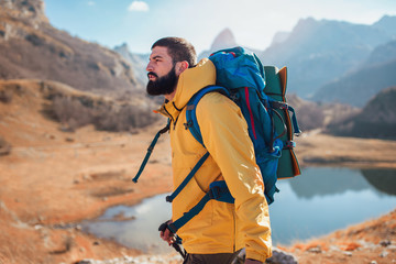 Man Traveler with backpack mountaineering .Travel Lifestyle concept lake and mountains on background Summer expedition vacations outdoor