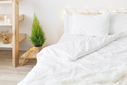 White cozy modern bedroom with holiday decoration. Bed with white bedding set, wooden rack with christmas ball and candles, little Christmas tree in a pot and led garland lights. Home christmas decor.