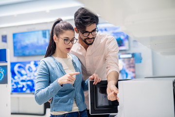 Young Caucasain couple looking for good quality microwave while standing in tech store..