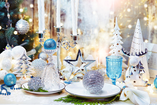 Christmas dinner background, plate, fork,  and festive decoration.Silver and cream Christmas table set.