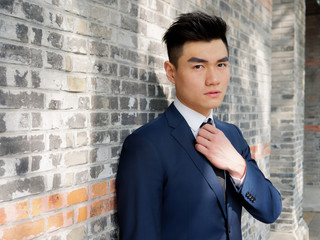 Portrait of a handsome businessman adjusting tie, close up upper body view. Attractive male hipster Chinese model.