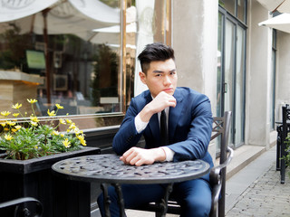 Portrait of a handsome businessman in blue suit sitting in a restaurant outdoor, close up upper body view. Attractive male hipster Chinese model.