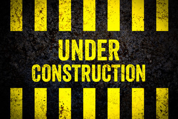 Under construction warning sign with yellow and black stripes painted over cracked concrete wall weathered texture background. Concept for do not enter the area, caution, danger, construction site.