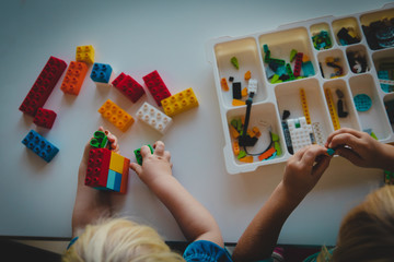 kids play with plastic blocks, building robot at school lesson