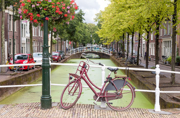 Delft city view in the Netherlands with water canal and vintage bicycle on the bridge in summer