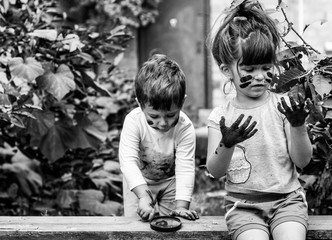 Toddler Boy and girl - dirty from playing in the mud. Children playing in the garden with dirty hands. Black and white.