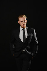 Young handsome confident man with beard standing on black background in suit. Leadership concept.