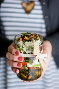 A woman holding a glass jar of lentil salad in her hands