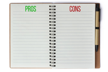 Pros and cons text words written on notepad with pen on the side and empty pages for text isolated on a seamless white background. Concept risk benefit assessment and business plan analysis.
