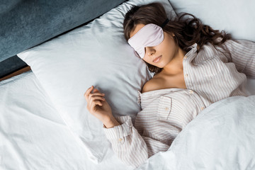 young brunette woman sleeping in eye mask in bed