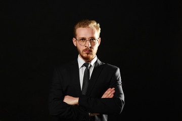 Close up portrait of sexy confident man with beard in glasses keeping arms crossed and on black background. Macho and gentleman concept.