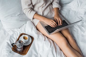 cropped view of woman with coffee using laptop in bed in the morning