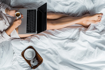 low section view of woman with morning coffee using laptop in bed