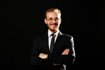 Close up portrait of successful man with beard in glasses keeping arms crossed and smiling on black background. Startup and business concept.