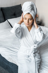 beautiful girl in white bathrobe wearing towel on head while sitting on bed