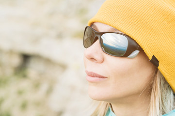 Close-up portrait of a girl traveler in a hat and climbing sunglasses. Happy girl on the background of rocks