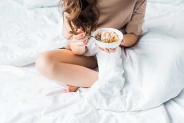 cropped view of girl having oatmeal for breakfast in bed
