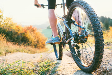 Mountain biker ride down from hill. Close up wheel image