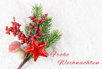 Christmas decoration, fir branch with berries and red star, card with the German words for merry Christmas