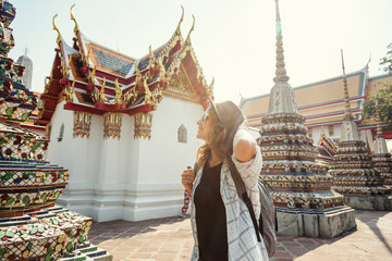 Young beautiful happy smiling european woman in a hat and glasses at a buddhist temple in Bangkok traveling to southeast Asia