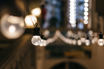 light bulbs garland. cafe exterior decor. closeup rows of lamps perspective with bokeh