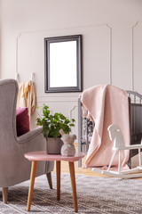 Table with plant next to armchair in kid's bedroom interior with mockup of empty poster. Real photo