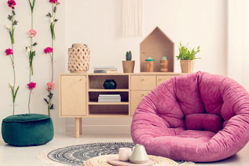 Pink settee in stylish interior with flower board and natural wooden furniture, real photo