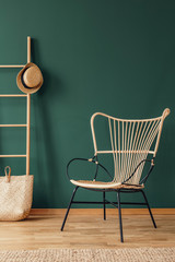 Rattan armchair next to bag and hat on ladder in green living room interior with rug. Real photo