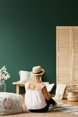 Woman reading book on carpet next to pouf in green living room interior with flowers. Real photo
