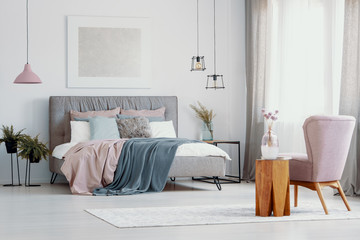 Pink armchair next to wooden stool in bedroom interior with poster above grey bed. Real photo