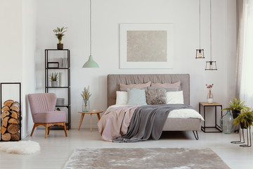 Pink armchair next to grey bed with blanket in bedroom interior with poster and plants. Real photo