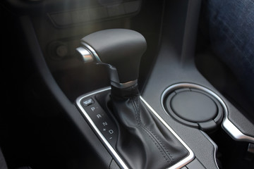 Car interior indoor. Black leather automatic gearbox with chrome button and sun rays, round ashtray