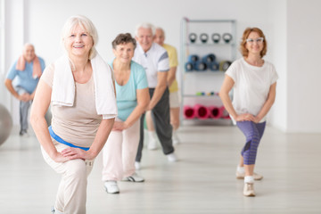Smiling senior woman with towel exercising during fitness classes for elderly people