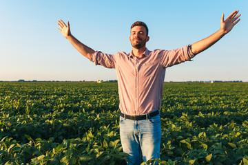 Portrait of young farmer standing in soybean field with his arms outstretched.