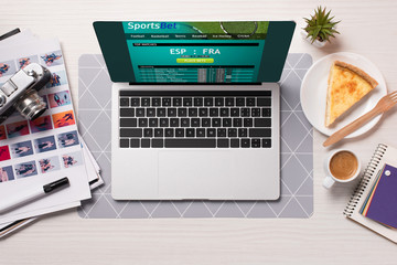 office desk with laptop with sports betting website on screen, flat lay