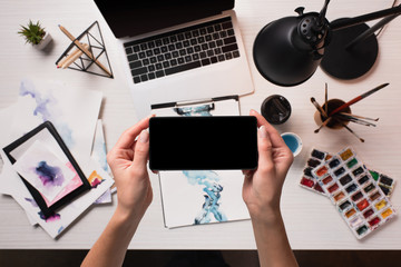 office desk with laptop, art supplies and cropped view of designer using smartphone with blank screen, flat lay