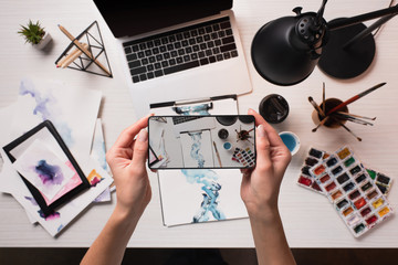 office desk with laptop, art supplies and cropped view of designer taking picture with smartphone, flat lay