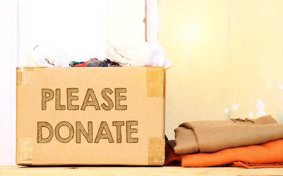 clothes in carton box on wood table for donation, coat drive concept, please donate text