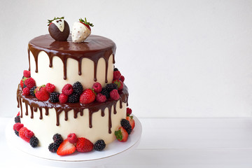Two-tiered wedding cake in chocolate, with slices strawberries, raspberries, blackberry, decorated with figures of the bride and groom on a white background.
