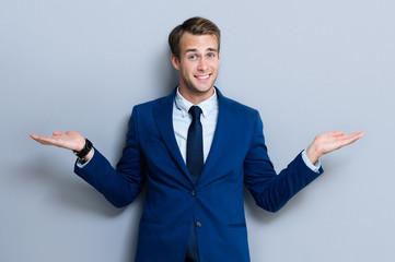 Smiling businessman showing something or copyspace