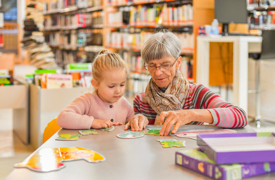 Granddaughter and grandmother put together a puzzle in the city library