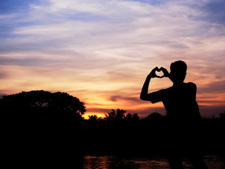 Silhouette of young man forming hand to heart shape, Sunrise scene, Silhouette photography.