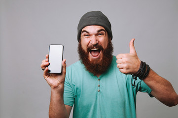 Excited man holding phone and showing thumbs up